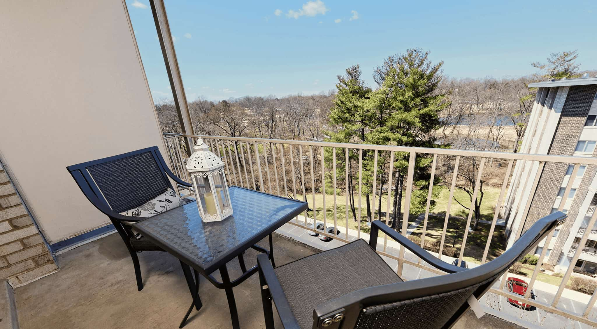 A table and two chairs sitting on a Congressional Towers Apartments balcony